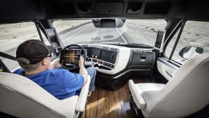 Wnętrze ciężarówki, kierowca zajmuje się tabletem, a nie prowadzeniem