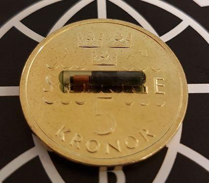 Mikroczip firmy BioHax na tle szwedzkiej monety. Źródło: Biohaxsweden.com