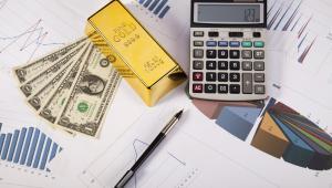 Kalkulator, sztabka, pieniądze i wykresy