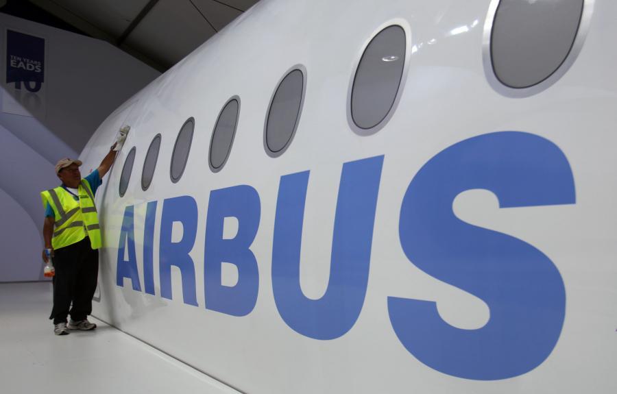 Jeden z pracowników Farnborough International Airshow czyści model samolotu Airbus SA A350, fot. Simon Dawson/Bloomberg