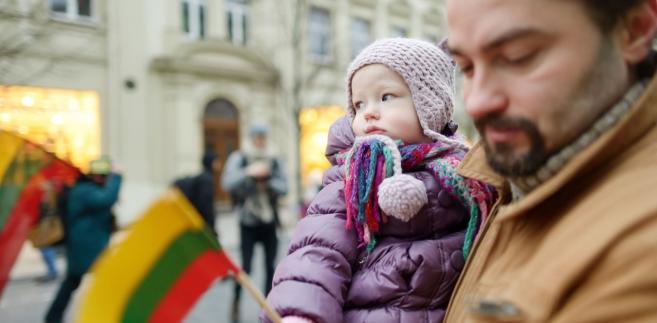Ojciec z dzieckiem, które trzyma litewską flagę
