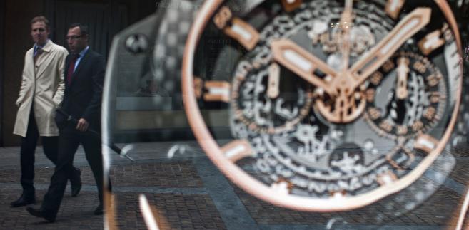 Genewa, przechodnie widoczni w oknie wystawowym sklepu z zegarkami